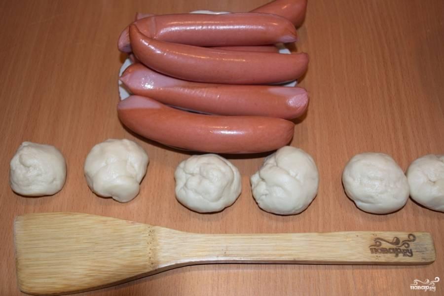 Подготовьте сосиски. Удалите с них пленку. Тесто разделите на шарики.