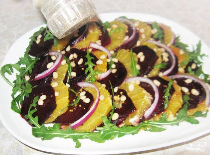 Полукольцами добавить красный лук и посыпать кедровыми орешками и поперчить.