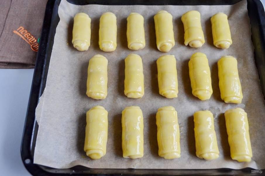 Разогрейте духовку до 200 градусов. Смажьте рулетики желтком. Отправьте на 20 минут пирожки в духовку.