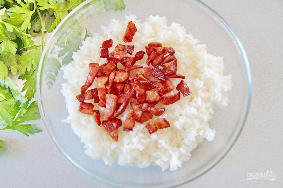 Рис отварите в слегка подсоленной воде, он должен быть мягким, но не разваренным. Бекон мелко нарежьте и обжарьте до хрустящей корочки. Соедините готовый рис и бекон вместе в глубокой миске или тарелке.