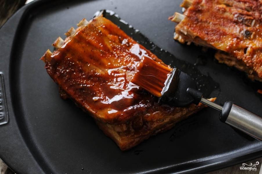 Разогрейте гриль. Рёбра достаньте из духовки и слегка остудите. Затем обильно обмажьте их соусом барбекю. Уже можно обжаривать рёбра на гриле. С каждой стороны обжаривайте их по 3-4 минуты.
