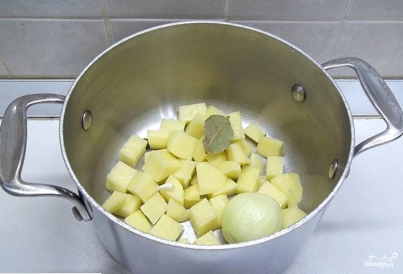 Картофель очищаем, нарезаем и помещаем в кастрюлю. Туда же кладем очищенную луковицу и перец горошком. Варим до готовности.