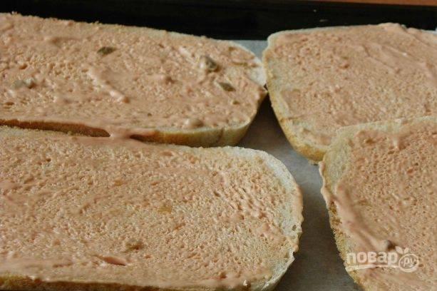 Хлебушек нарежьте на ломики около сантиметра толщиной. Можно использовать уже нарезанный батон. Смажьте каждый кусочек смесью кетчупа и майонеза.