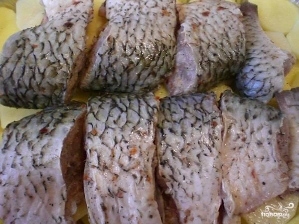 На картофель выкладываем рыбу. Сверху лук.