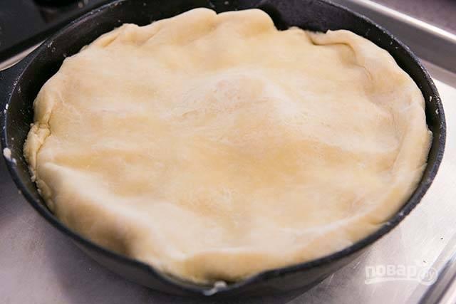 7.Достаньте тесто из холодильника и раскатайте его в круглый пласт. Пластом теста накройте груши, засуньте поглубже края.
