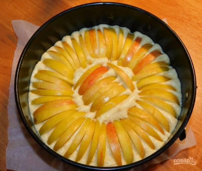 Яблоки нарежьте на тонкие дольки и выложите по всему тесту. Поставьте в духовку при 180С минут на 40. Готовый пирог остудите в форме.