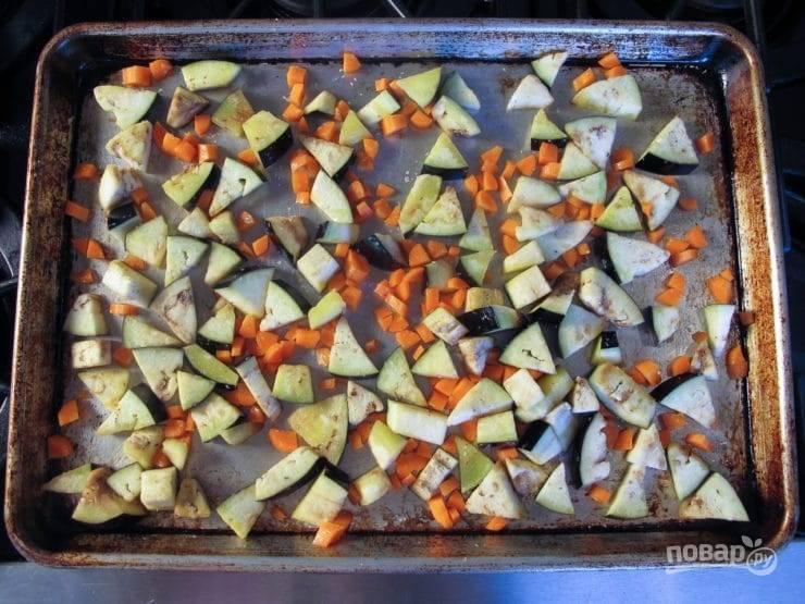 2. После этого подготовьте овощи. Нарежьте мелкими кубиками морковь. Баклажан нарежьте небольшими кусочками. Выложите всё на противень. Сверху влейте 2 ч. ложки масла, всыпьте 0,5 ч. ложки соли.