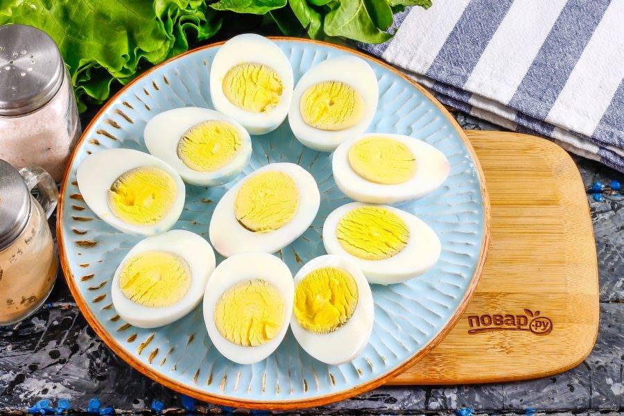 Остывшие отварные куриные яйца очистите от скорлупы, промывая в воде. Разрежьте каждое пополам, и выложите половинки на тарелку.