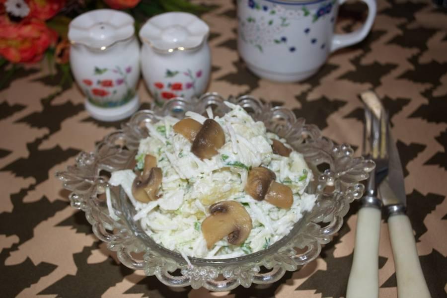 Заправьте салат сметаной. Добавьте соль, чеснок (его нужно выдавить через пресс). Перемешайте. Выложите салат на тарелку. Украсьте нарезанными маринованными шампиньонами.
