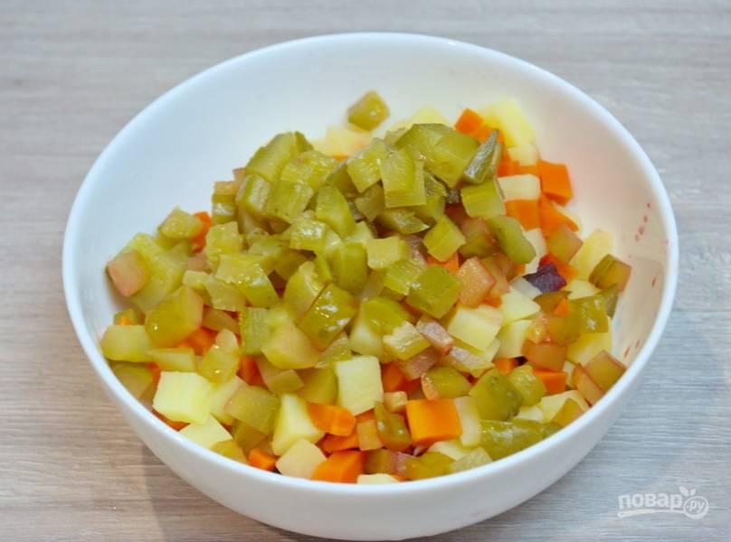 Картофель и морковь откиньте на сито, дайте стечь жидкости полностью. Добавьте овощи в салатник. Нарежьте соленые огурцы, добавьте их в салатник.
