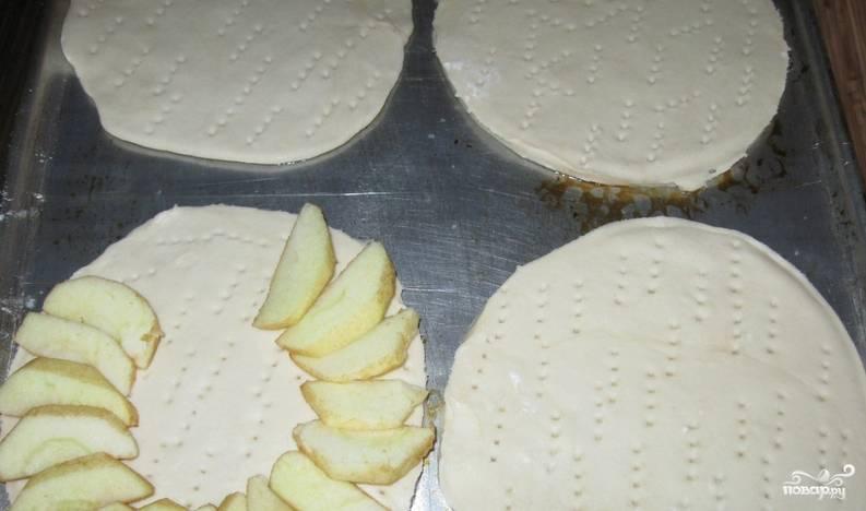 Очень тонко раскатываем слоеное тесто (5-6 мм.). При помощи тарелки вырезаем из теста четыре круглых коржа. Выкладываем их на противень, смазанный маслом. Накалываем тесто вилкой, присыпаем сахаром, сверху выкладываем дольки яблок.