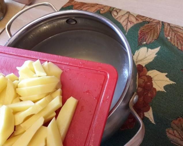 Бульон вылейте в кастрюлю, доведите до кипения и бросьте в него порезанный картофель. Отварите до готовности.