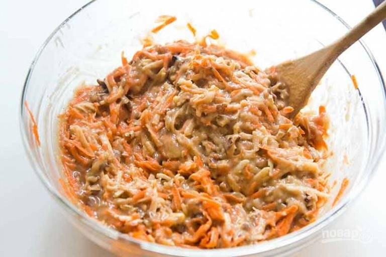 2.Добавьте в миску растительное масло, яйца, тертую на крупной терке морковь и яблоки, кокосовую стружку, грецкие орехи. Все тщательно перемешайте.