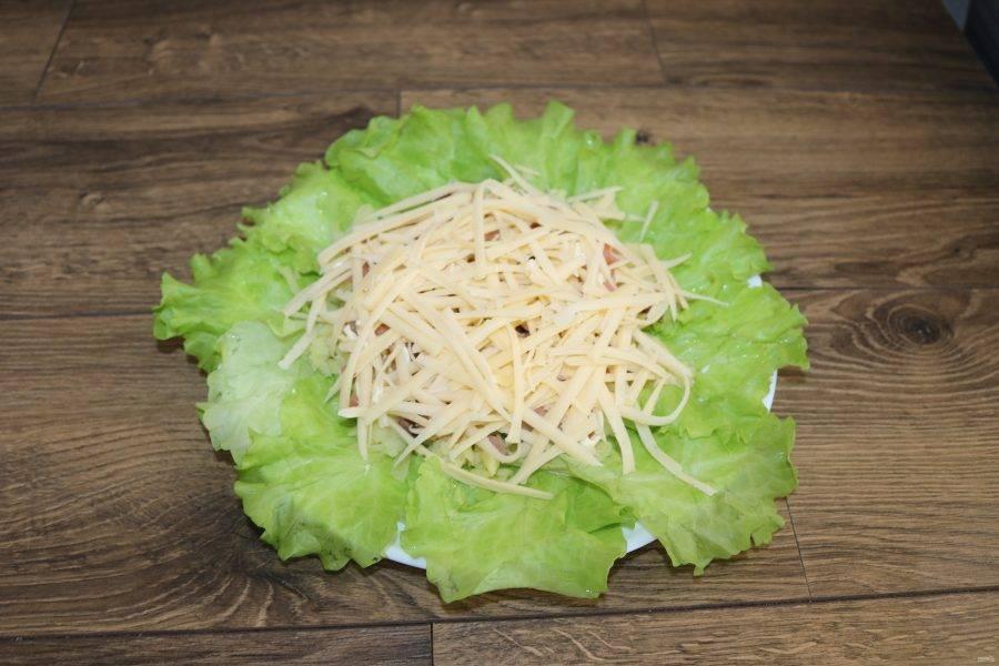 Затем натрите на крупной тёрке сыр и сделайте сеточку майонеза.