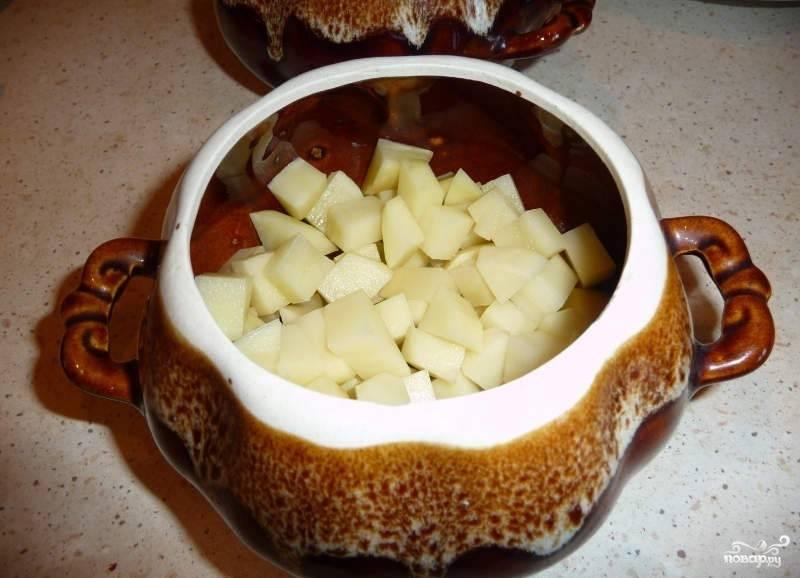 Теперь необходимо разложить все ингредиенты по горшочкам. Первым слоем идет картофель.