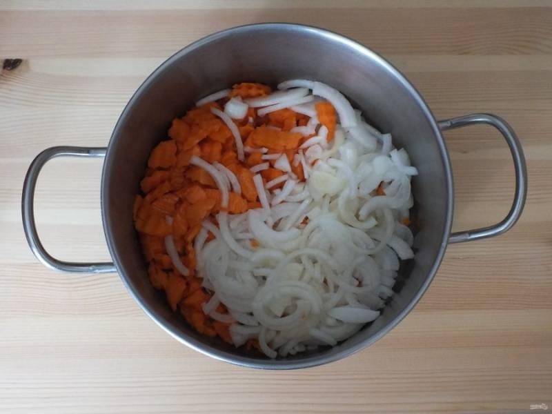 Очищенную морковь нарежьте шайбочками или половинками шайбочек, лук полукольцами. Переложите овощи в кастрюлю с толстым дном. Добавьте 50 мл. растительного масла.