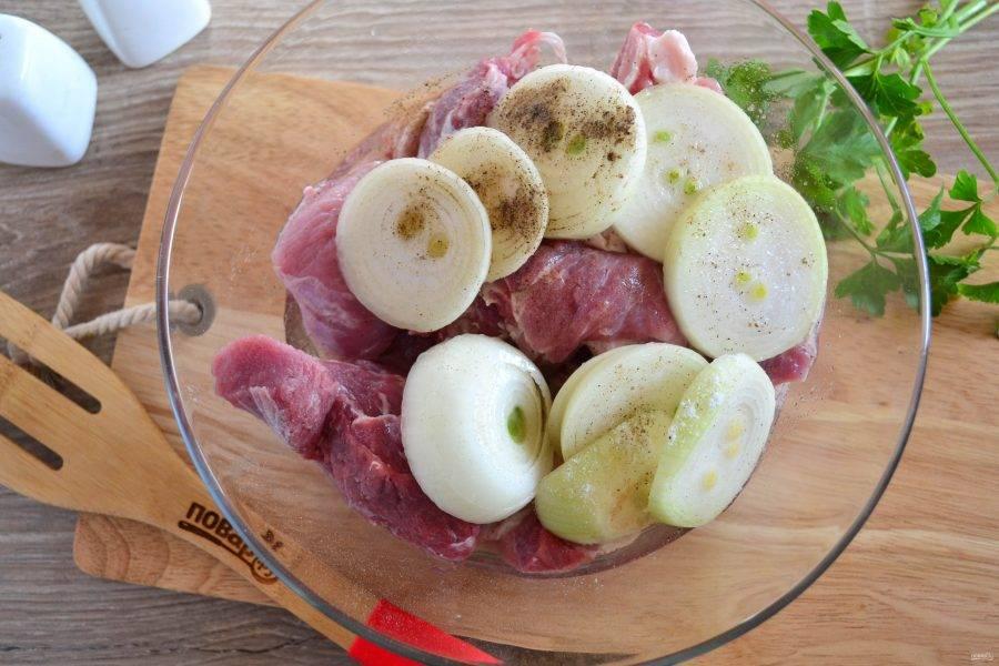 В большую миску сложите мясо, добавьте лук, порезанный крупными кольцами, посолите, поперчите по вкусу, влейте яблочный уксус.