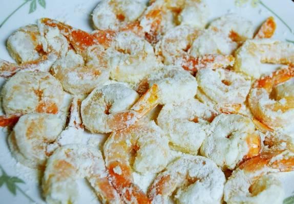 Смешайте майонез и тайский соус. Обмакните очищенные креветки в приготовленный соус, а затем обваляйте в крахмале.