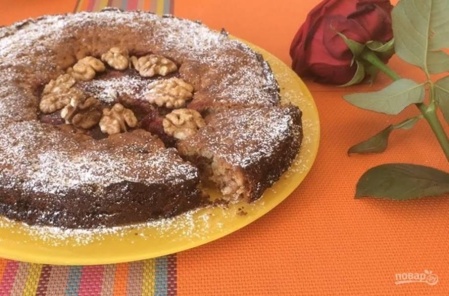 3. Вилкой разровняйте тесто. Отправьте пирог в разогретую до 190 градусов духовку 30 минут. Остудите пирог и посыпьте сахарной пудрой, украсьте орешками. Приятного аппетита!