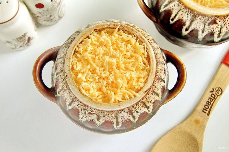 Распределите оставшуюся сметану и посыпьте все тертым сыром. Накройте горшочки крышками и готовьте при температуре 180 градусов в течение 1 часа.