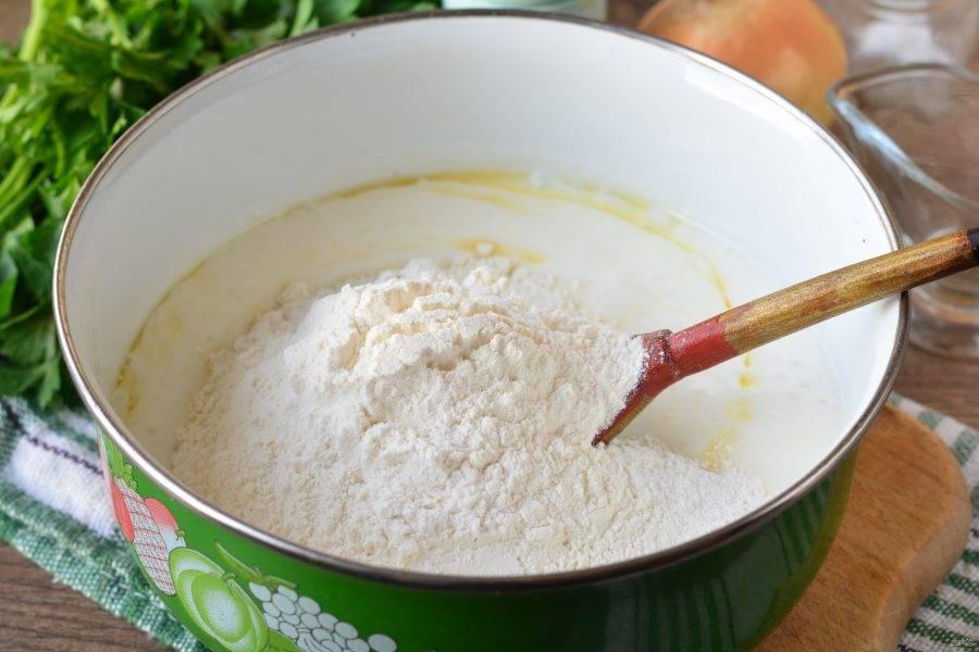 Всыпьте просеянную пшеничную муку и начните замешивать тесто.