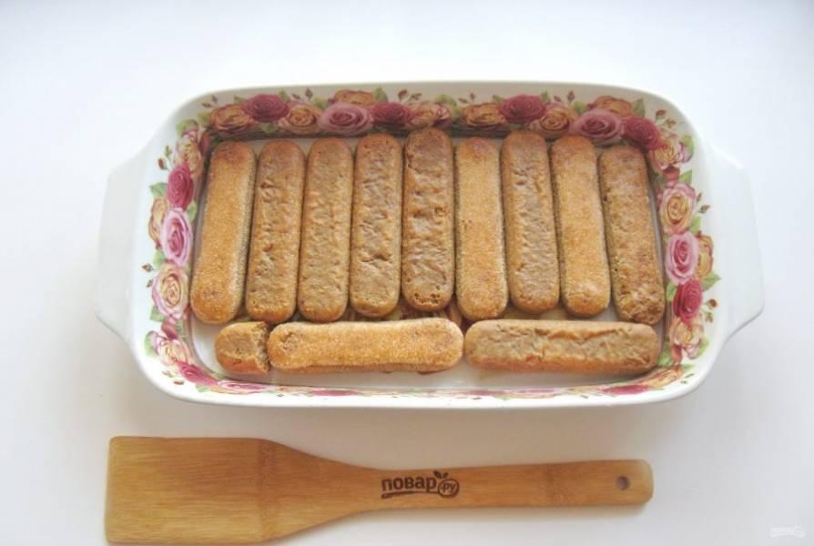 Быстро макайте печенье в кофе с коньяком и выкладывайте в форму. Выложите таким образом 12 штук печенья.