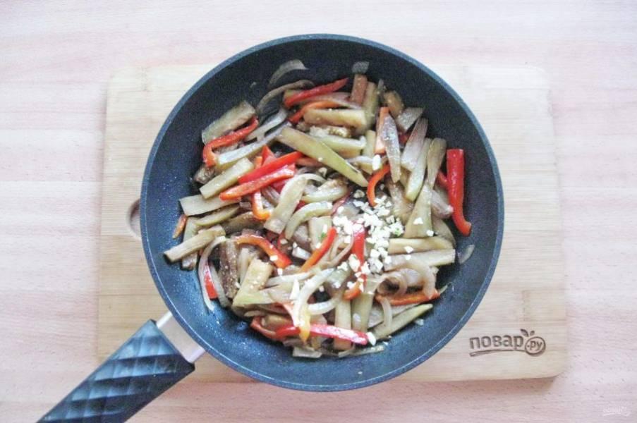 Чеснок очистите и мелко нарежьте. Выложите в сковороду с баклажаном, луком и перцем.