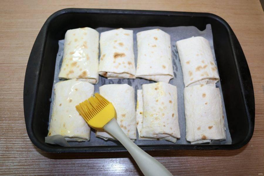 Смажьте рулетики маслом при помощи кулинарной кисти.