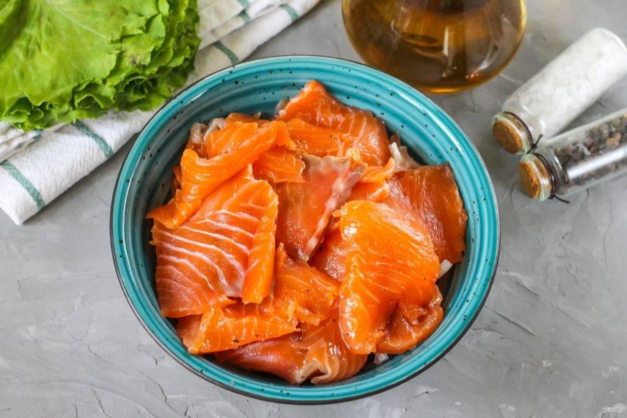 Засоленную мякоть горбуши нарежьте тонкими лепестками и выложите в емкость с луковой нарезкой и зеленью.