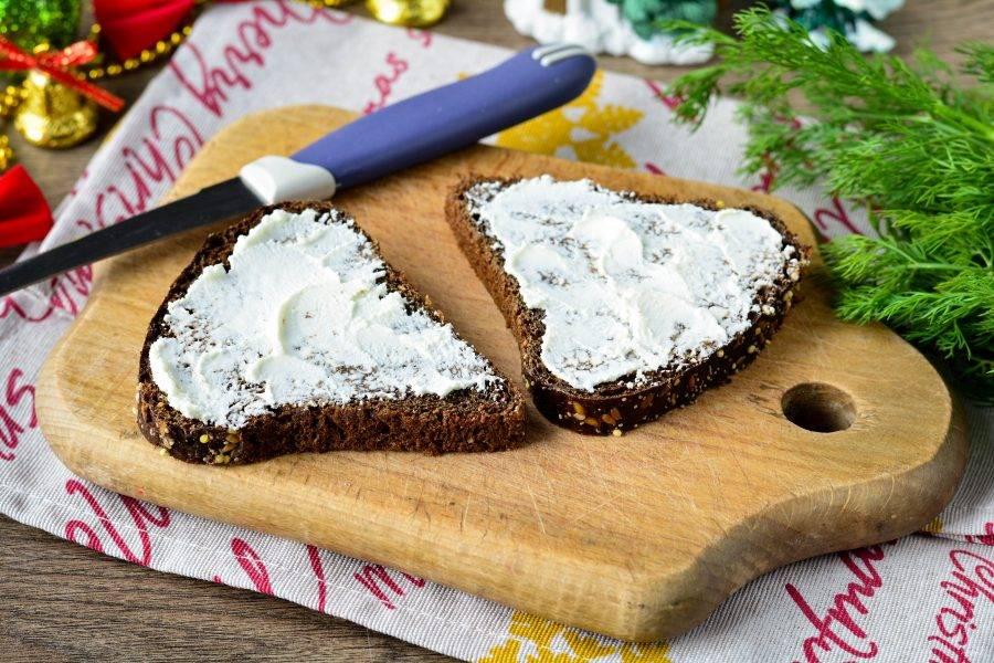 Смажьте хлеб сливочным мягким сыром.