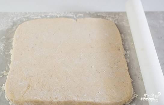 Готовое тесто присыпьте мукой и раскатайте в пласт толщиной в 7 мм.