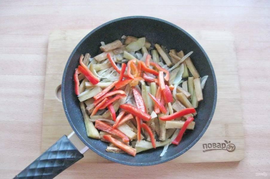 Болгарский перец очистите от семян и помойте. Нарежьте соломкой и выложите в сковороду с баклажаном и луком.