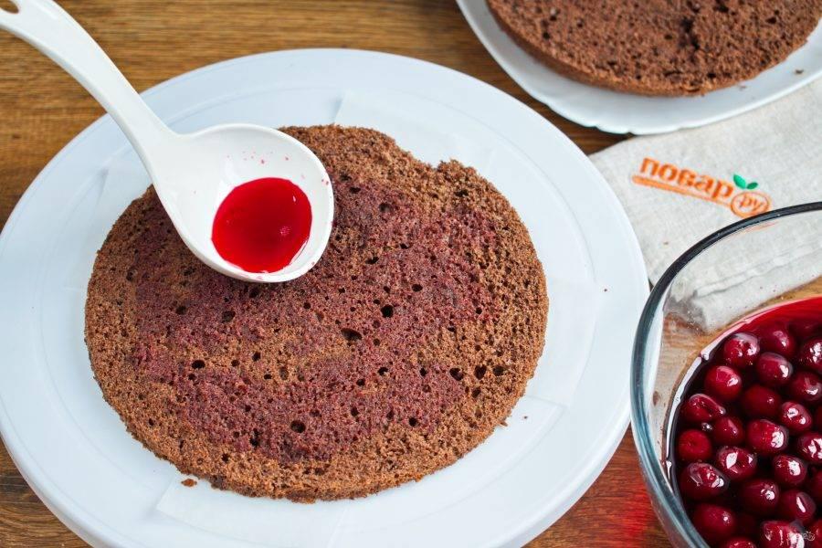 Бисквит разрежьте на 4 коржа. Каждый пропитайте сиропом, в котором замачивалась вишня. Вишню откиньте на сито.