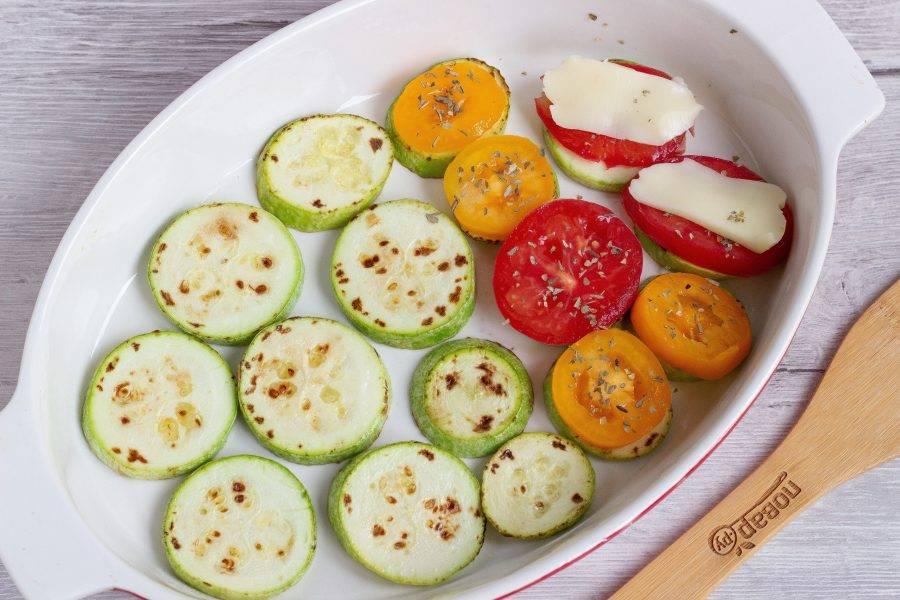 Выложите кабачки в форму для запекания. Сверху положите помидоры, посыпьте орегано и последним слоем – кусочки сыра.