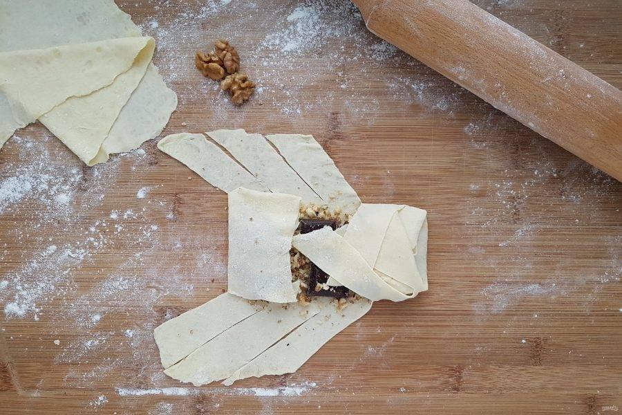 Для того чтобы сделать косичку, мысленно разделите пласт теста на три части. На середину положите орехи и шоколад. По бокам сделайте симметричные разрезы. Подверните тесто с боков, а затем чередуя полоски, заплетите косичку.