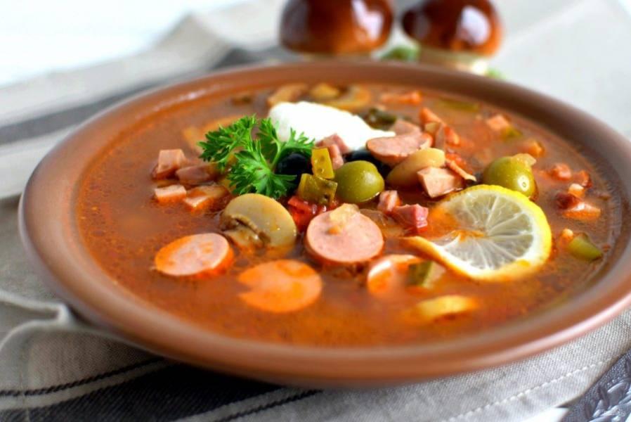 Подавайте солянку горячей. При подаче положите в тарелки ломтик лимона и добавьте сметану. Приятного аппетита!