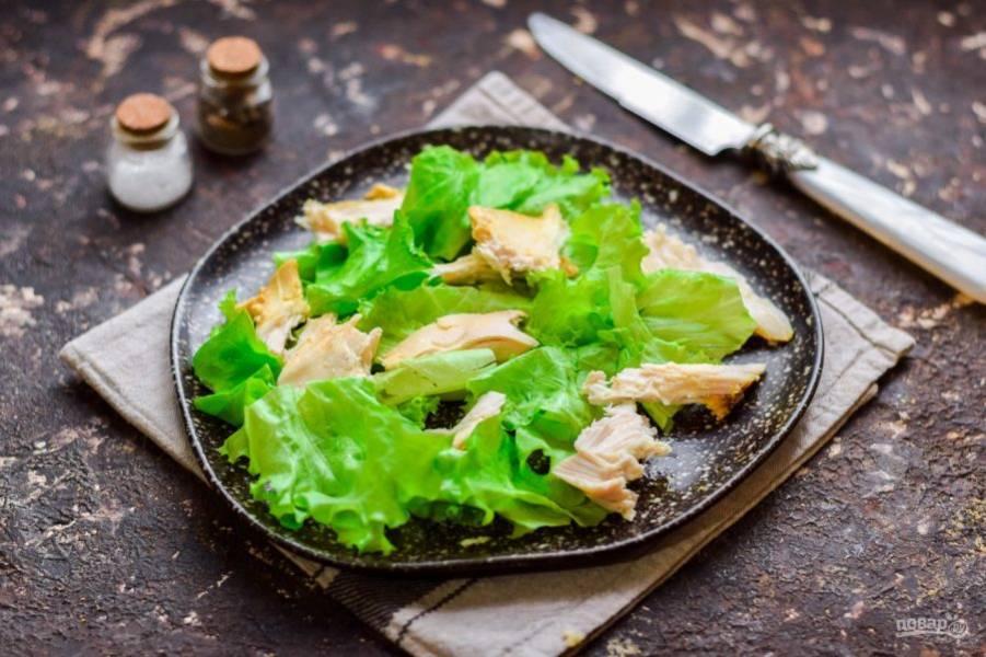 Салатные листья сполосните, просушите, порвите и выложите на тарелку. Заранее запеките филе курицы, немного остудите и крупно нарежьте, добавьте к листьям.