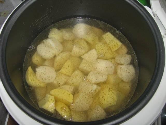 Вместе с рыбой мы можем приготовить и гарнир. Поэтому очистим примерно 500 г. картошки, порежем овощ кубиками и выложим в чашу мультиварки. Заливаем водой так, чтобы уровень воды был чуть выше картошки.
