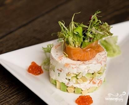 Снимаем кольцо , украшаем салат. Для этого пластик семги сворачиваем с листиками салата и выставляем на салат. Рядом вкладываем икру.