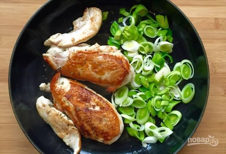 2.Измельчите чеснок, нарежьте кружочками лук-порей. Выложите овощи к обжаренной курице, обжарьте их до мягкости.