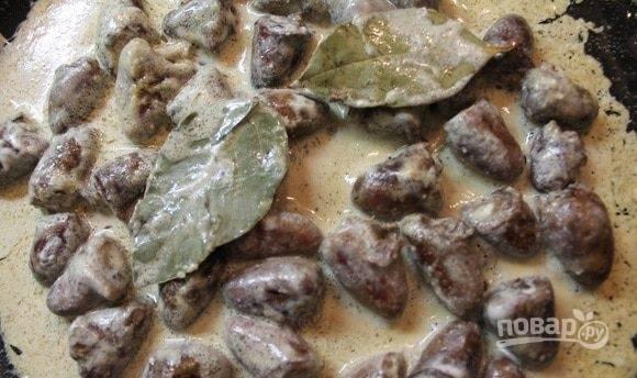 Затем в сковороду добавьте сметану, лавровый лист, соль и приправу по вкусу. Перемешайте ингредиенты.