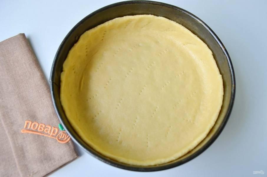 2. На рабочем столе раскатайте тесто чуть больше диаметра формы. С помощью скалки перенесите его в смазанную маслом форму. Проколите вилочкой. Уберите форму с тестом в морозилку на 15 минут.