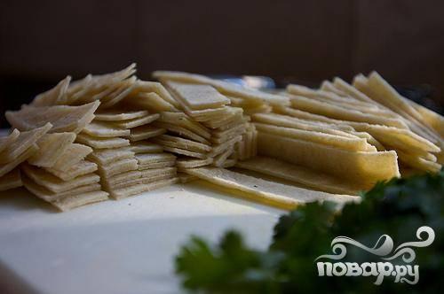 3. Разрезать кукурузные лепешки пополам, затем разрезать их крест-накрест на полоски размером 1 см и добавить в суп.