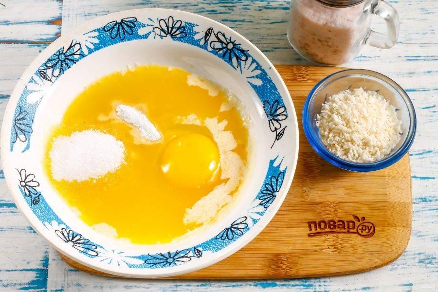 Слегка остудите масло, чтобы в нем не сварилось яйцо. Вбейте в емкость куриное яйцо, всыпьте сахар, соль, разрыхлитель. Взбейте все вилкой или венчиком.