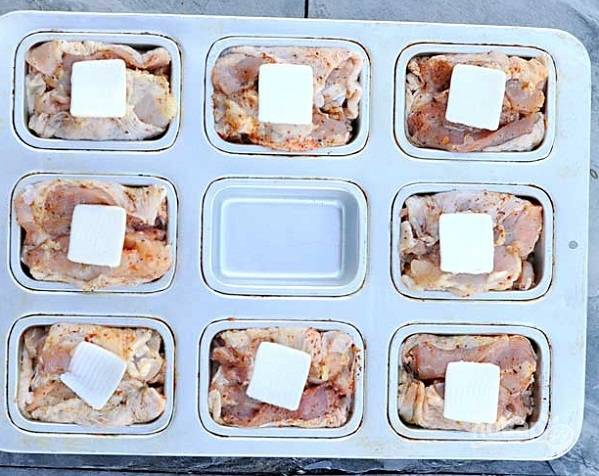 4. Нарежьте небольшими кусочками сливочное масло. Выложите по кусочку на дно формы. Добавьте по 1-2 ложки бульона. Разложите бедрышки. Сверху выложите еще по кусочку масла.