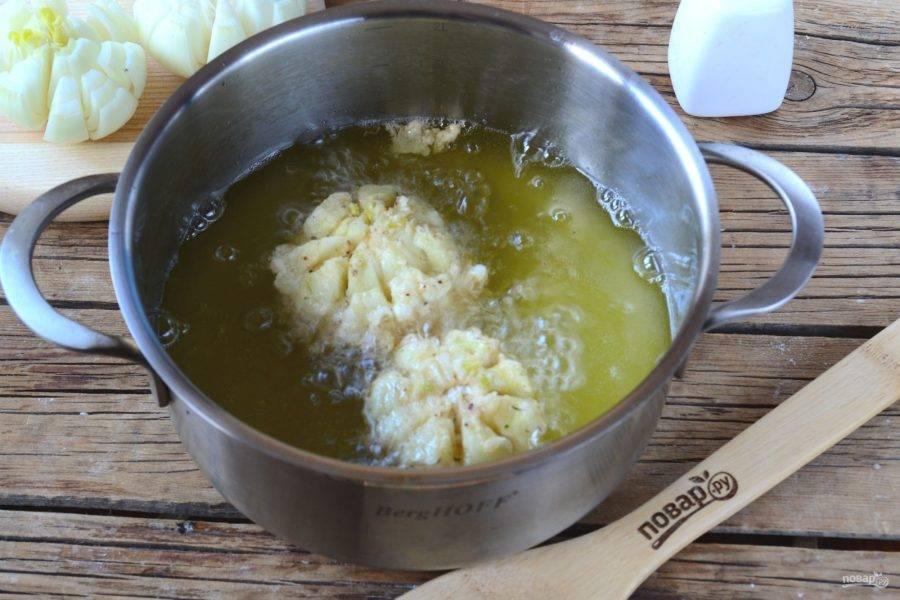 Разогрейте растительное масло в сотейнике или толстодонной кастрюле. Как только масло хорошенько прогреется и начнет слегка потрескивать, отправьте в него луковицы. Время от времени проворачивайте луковицы, чтобы они максимально равномерно прожарились и обрели красивый золотистый цвет.