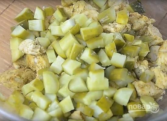 Выкладываем остывшее филе в миску. Огурцы нарезаем небольшими кубиками. Количество огурцов зависит от вашего вкуса.
