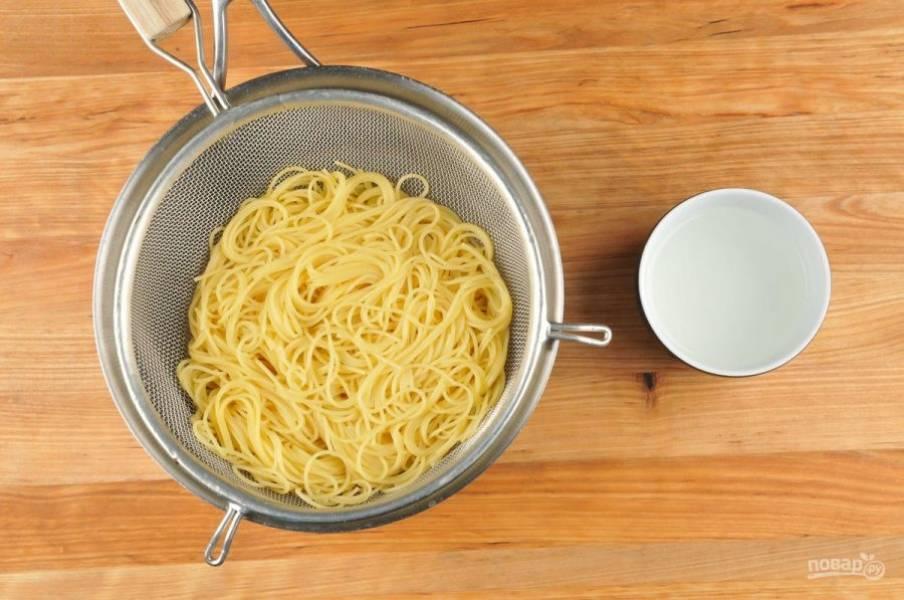 """4. В это же время отварите пасту до состояния """"аль денте"""" в кипящей воде. Сохраните 1 стакан воды из-под пасты. А сами спагетти промойте, а потом перемешайте с маслом."""