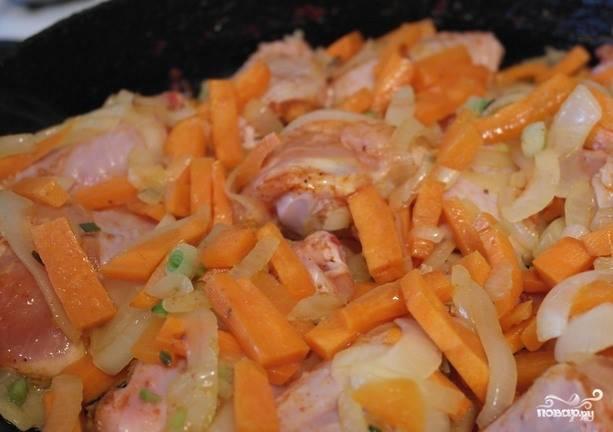Когда овощи на сковороде немного протушатся, выложите к ним куриные крылышки.Перемешайте все ингредиенты так, чтобы куриные крылышки оказались внизу, а овощи — сверху. Так мясо прожарится быстрее.