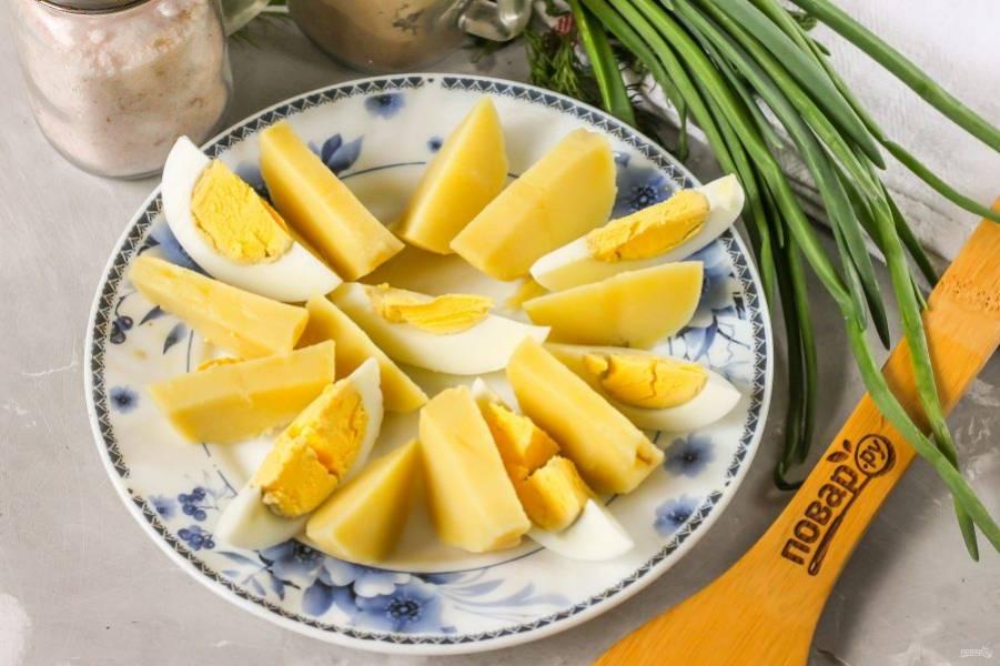 Картофель и куриное яйцо отварите заранее и остудите в воде. Затем счистите с картофеля кожуру, а с яйца - скорлупу и промойте их в воде. Нарежьте дольками и выложите на тарелку.